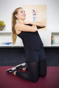 Junge Frau auf roter Trainingsmatte macht Beckenbodenübungen