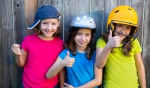 Drei glückliche Kids mit Sporthelmen