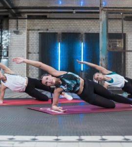 3 junge Frauen trainieren auf bunten Yogamatten und machen den Seitstütz