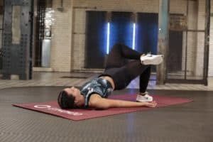 Junge Frau macht Po Übung Hip Lifts auf roter Trainingsmatte
