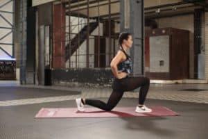 Junge Frau macht Lunges auf roter Trainingsmatte