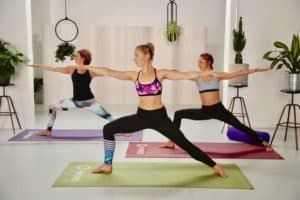 3 Frauen machen Yoga Krieger 2 auf bunten matten in hellem loft