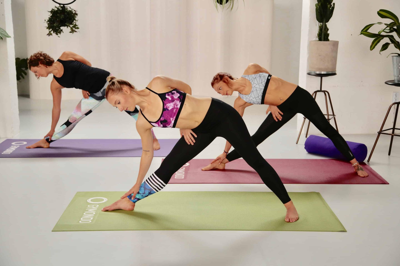 3 Frauen machen Yoga Dreieck auf bunten matten in hellem loft
