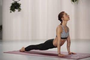Frau macht Yoga heraufschauender Hund auf roter trainingsmatte