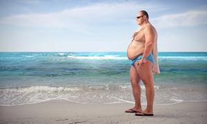 Einsamer Mann mit Bierbauch am Strand