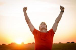 Mann mit zum Jubel erhobenen Armen vor einem Sonnenuntergang
