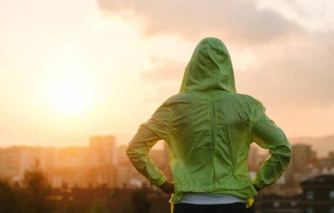Frau mit grünem Kapuzenpulli schaut in den Sonnenuntergang.