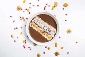 Weiße Schale mit Schokoladen Frühstücksbrei garniert mit Bananenscheiben und gehobelten Mandeln