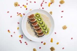 weiße Schale mit Quinoa Frühstücksbrei garniert mit Kiwi und Feigen