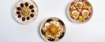 3 weiße Schalen mit Haferbrei garniert mit Früchten und Nüssen, Oat Meal Bowls