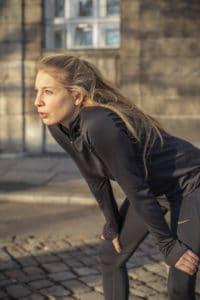 Frau beim Lauftraining in Laufkleidung atmet durch, die Hände auf die Knie gestützt.