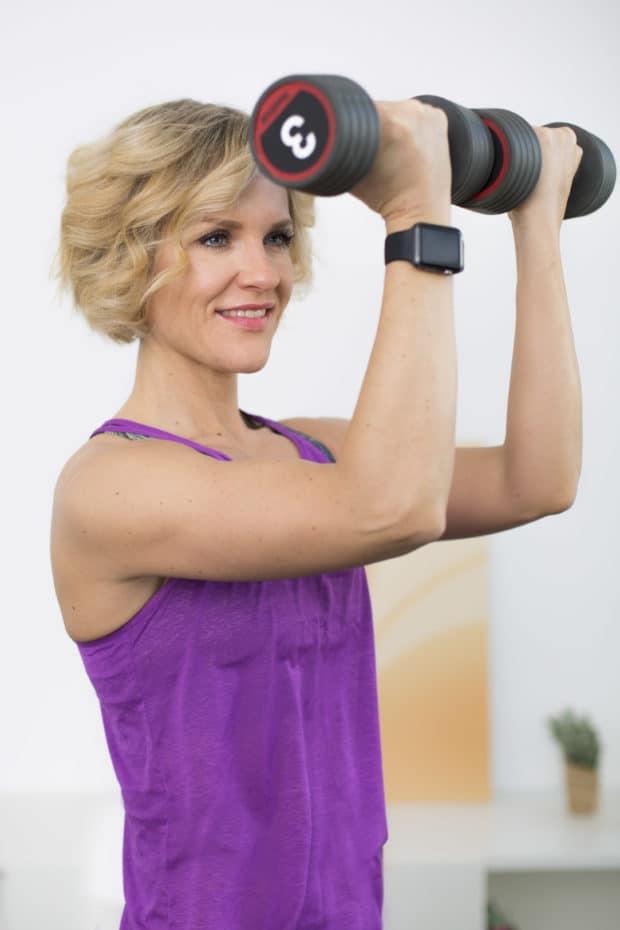 Junge Frau macht Fitnessübung Arnold Press