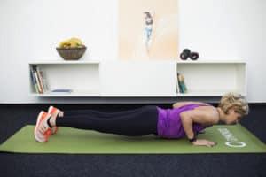 Junge Frau macht Fitnessübung Triceps Push Up