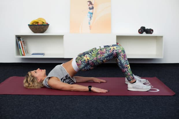 Junge Frau macht Fitnessübung Hip Bridge