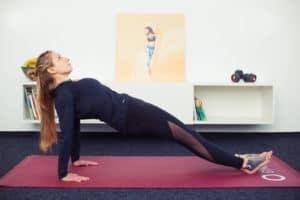 Junge Frau macht Rückenübungen auf roter Trainingsmatte Reverse Plank