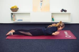 Junge Frau macht Rückenübungen auf roter Trainingsmatte Latzug