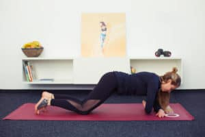 Junge Frau macht Rückenübungen auf roter Trainingsmatte Side Plank