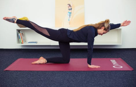 Junge Frau macht Rückenübungen auf roter Trainingsmatte All Fours