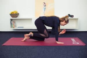 Junge Frau macht Rückenübungen auf Trainingsmatte Diagonales Zusammenziehen