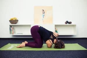 Junge Frau macht Beweglichkeitsübung auf grüner Fitnessmatte