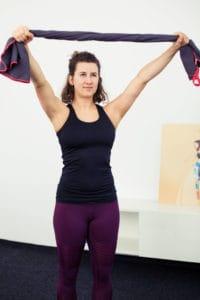 Junge Frau macht Beweglichkeitsübung für die Schulter mit Handtuch