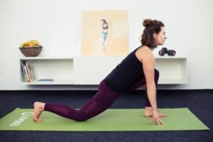 Junge Frau macht Beweglichkeitsübungen auf grüner Matte Lunge & Runners Stretch