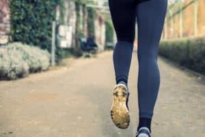 Beine einer jungen Frau in Sportleggins die joggt