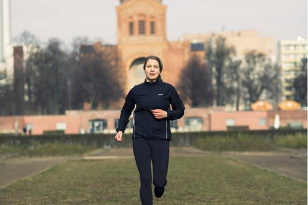Junge Frau in schwarzer Funktionskleidung joggt durch den Park
