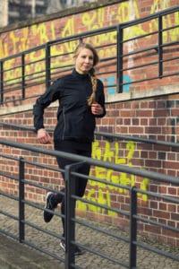 Junge Frau in schwarzer Funktionskleidung joggt eine Steigung hoch