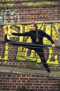 Junge Frau macht Dehnübungen für die Beine nach dem Lauftraining