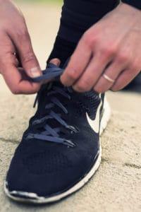 Ein schwarzer Sportschuh wird von den Händen einer Frau geschnürt