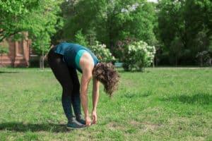 Junge Frau auf einer Raststätte macht Übung Roll Up