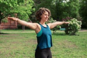 Junge Frau auf einer Raststätte macht Übung Schulterkreise