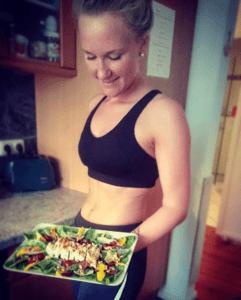 Frau lächelt und hält teller mit salat