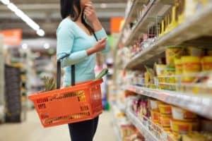 Frau mit Einkaufskorb zwischen den Regalen eines Supermarktes überlegt welche Lebensmittel sie kaufen soll