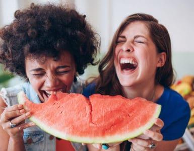 Zwei junge Frauen lachen und essen zusammen ein großes Stück Wassermelone