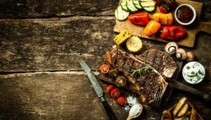 Tisch mit Fleisch und Gemüse und einem Messer