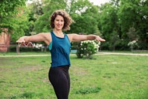 Junge Frau auf einer Raststätte macht Übung Torso Twist