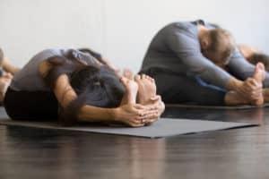 Eine Frau und ein Mann auf Yogamatten machen die sitzende Vorbeuge