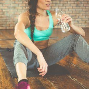 Sportlerin trinkt Wasser um abzunehmen