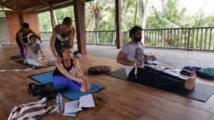 Yogaklasse auf Bali, Yogalehrerin korrigiert eine junge Frau in der Vorbeuge