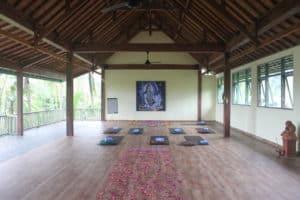 Yogamatten liegen in einem offenen Yogaraum auf Bali