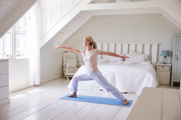 Frau macht Yoga nach dem Aufstehen