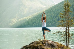 Frau macht Yoga Übung am See