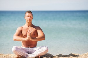 Mann in weißer Hose macht Yoga am Strand