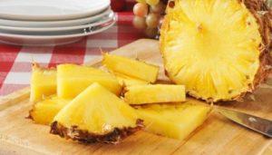Geviertelte Ananasscheiben auf einem Holzbrett