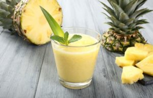 Ananassaft in einem Glas, dahinter eine aufgeschnittene Ananas
