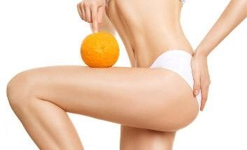 Frau, die eine Orange auf ihrem cellulite-freien Oberschenkel balanciert