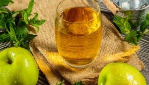 Glas Apfelsaft neben zwei grünen Äpfeln