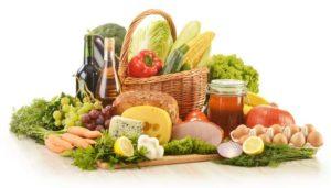 Obst, Gemüse und tierische Produkte versammelt in und um einen Korb herum